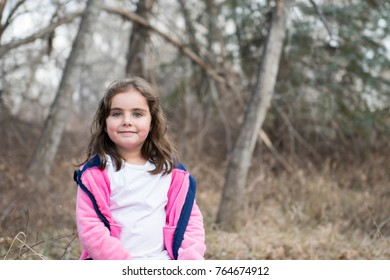 Young Girl Playing Outside in a Playground & Wooded Area on a Fall Day