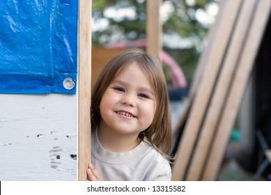 A young girl playing peek-a-boo around a corner