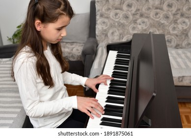 Young girl playing the piano. Child practicing on the modern electric piano at home. Music lesson.