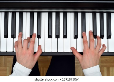 Young girl playing the piano. Child practicing on the modern electric piano at home. Music lesson. Close-up. High angle view.