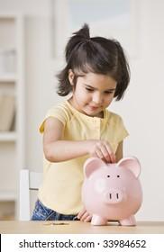 Ein junges Mädchen spielt mit einem Sparschwein.  Sie schaut von der Kamera weg.  Vertikal gerahmte Aufnahme.