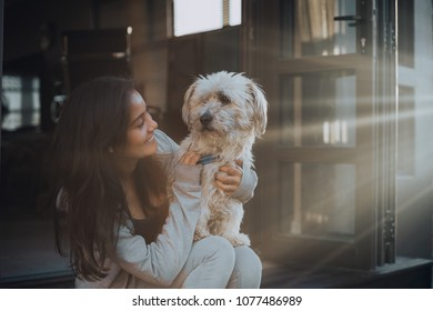 Young girl playing with small dog at sunset