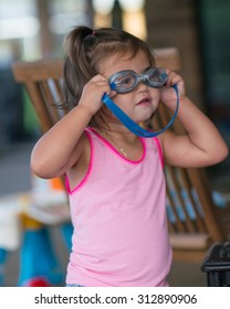 Young Girl Playing with Swimming Googles