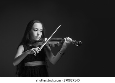 The young girl playing the violin in black and white on the dark background