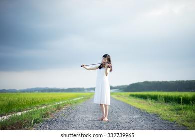 young girl playing violin on a country road