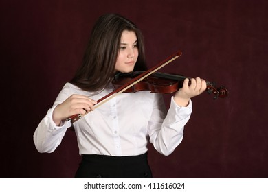 Young girl playing violin, on dark background