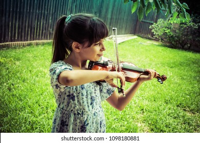 Young girl playing violin outdoors student