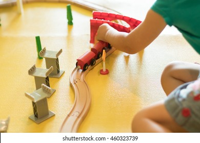 young girl playing with wooden train set, on a yellow playroom floor