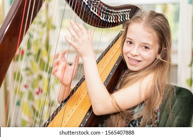 A young girl plays harp and looks at the camera with a smile