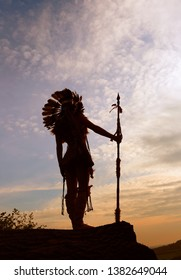 A young girl plays the part of a native American Indian. She dresses up wearing a feathered headdress and poses outdoors with the sun setting in the distance.