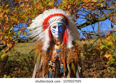 A young girl plays the part of a native American Indian  girl. She wears a white feathered headdress and her face is painted blue and white.
