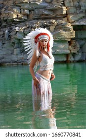 A young girl plays the part of a native American Indian. She dresses up all in white wearing a white feathered headdress  and is seen in a stone quarry lake.