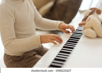 A young girl plays the piano at home