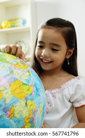 Young girl pointing at a globe