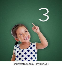 Young girl points finger with number three