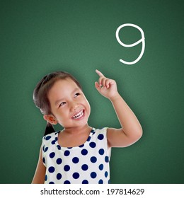 Young girl points finger with number nine