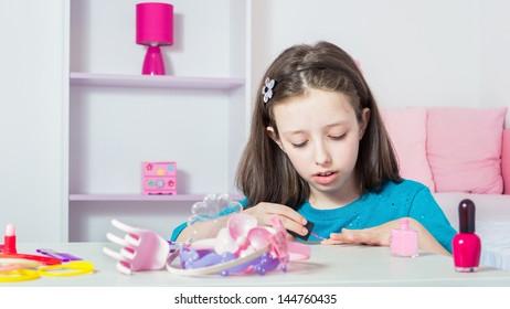 Young girl polishing her nails