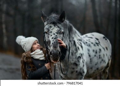 Young girl portrait with Appaloosa horse in rainy autumn park