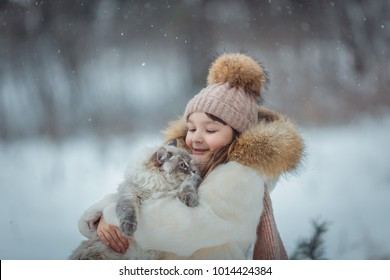 Young girl portrait with cat in winter park