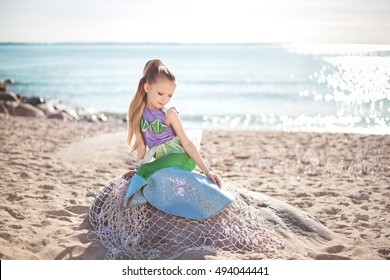 Young girl portrait in mermaid costume on the beach near sea