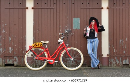 A young girl poses for the camera dressed as a hippie.  She stands by a red vintage bicycle smiling and drinking  out of an old soda bottle.