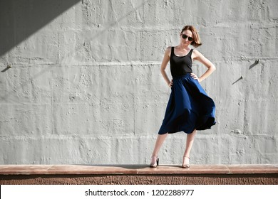young girl posing against a concrete wall, dressed in black, hard light and shadows