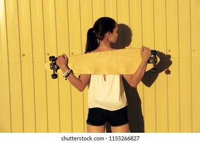 Young girl posing with her skateboard behind her back in front of yellow fence with copyspace