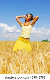 Young girl posing on plant of wheat in sunny day