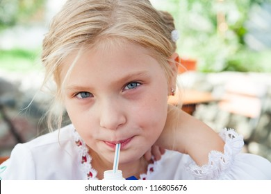 Young girl  posing in an outdoor cafe and sipping juice with a straw