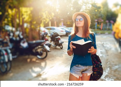 Young girl posing in the street with a notebook