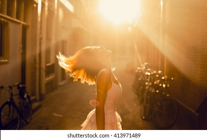 young girl posing in the street on sunset lights, hair style, amazing, drees, amsterdam city, moods happy dance