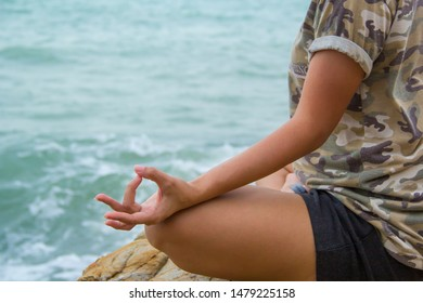 Young girl posting yoga position on the cliff with sea background. Healthy concept.