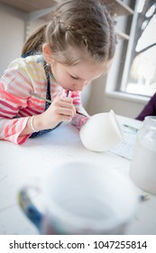 Young girl in pottery workshop decorating a cup
