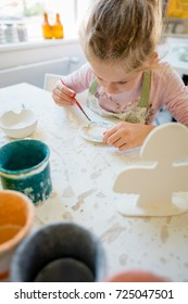 Young girl in pottery workshop decorating small plate