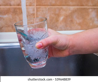 Young girl is pouring water into the glass
