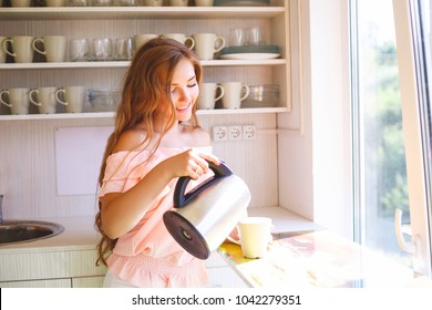 The young girl pours in a mug some tea from the electric kettle in kitchen