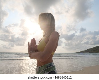 Young girl practice mountain yoga posture at seashore in sunshine.