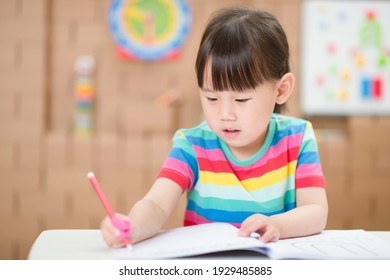 young girl practice writing letters for homeschooling