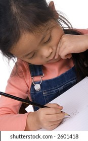 A young girl practices writing her letters