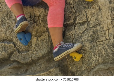 Young girl practicing rock climbing on artificial outdoor climbing wall. Close-up on her feet.