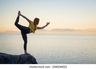 Young girl is practicing yoga during a vibrant sunset. Taken in Whytecliff park, Horseshoe Bay, Vancouver, BC, Canada.