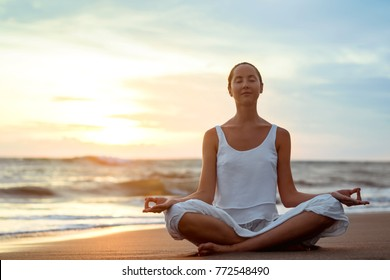 Young girl practicing yoga on the beach