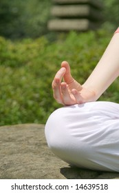 Young girl practising yoga in the park on sunny day