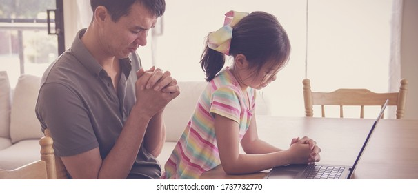 Young girl praying with father parent with laptop, family and kids worship online together at home, streaming church service, social distancing concept