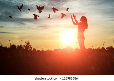 A young girl prays while enjoying nature amidst a beautiful sunset. The concept of hope, faith, religion. A flock of birds flies, a symbol of hope and freedom.