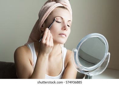 A young girl  prepares to go out. She is sitting at sofa next to the window and doing makeup, in front of a mirror, at her home. She applieds with a brush eyeshadow on the eyelids.