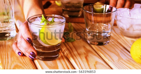 A young girl is preparing an alcoholic or non-alcoholic cocktail. hands, bartender, bar, restaurant, mint, lime, lemon, alcoholic, non-alcoholic