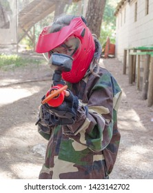 Young girl is preparing her gun for play on the paintball playground in the forest. She has red safety helmet fatigues and red gun full of yellow bullet.