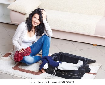 Young girl preparing her luggage before travel. She is in doubt of what to pack