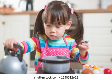 young  girl pretend play food preparing  in the against real kitchen background